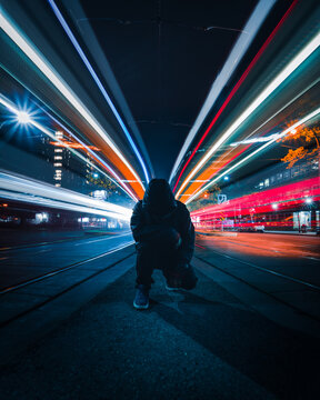 Time-lapse photo of person between vehicles during nighttime