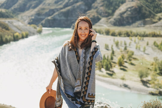 Carefree brunette young woman traveler in poncho on background of the mountain river