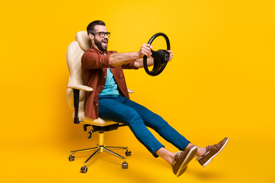 Full length body photo of playful crazy man in chair holding steering wheel pretending car rider isolated vivid yellow color background