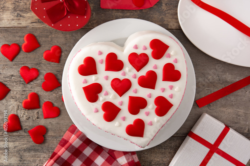 Heart cake for St. Valentine's Day, Mother's Day, or Birthday, decorated with sugar hearts on wooden table