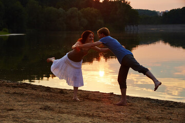 Fototapeta Side View Of Happy Couple Standing On One Legs At Lakeshore During Sunset obraz