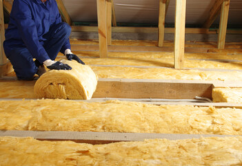 Worker thermally insulating house attic with glass wool