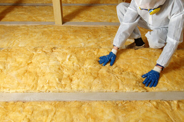 Obraz Worker thermally insulating house attic with glass wool - fototapety do salonu