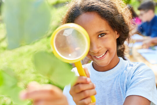 Girl in summer camp looks through magnifying glass at a sheet