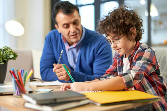 Father's help. Caring middle aged latin father helping, discussing homework with his son, school child while sitting together at the desk at home