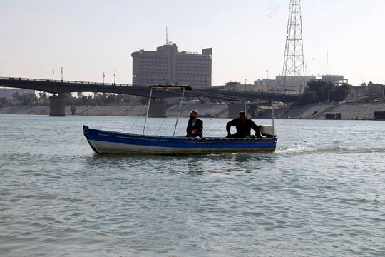People use a boat to travel between the banks of the Tigris river to avoid the traffic jams in Baghdad