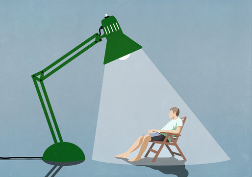 Man sitting under bright sun lamp