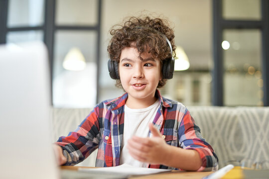 Modern approach to learning. Portrait of joyful latin american little boy wearing headphones, looking at the screen of a laptop while having online lesson at home