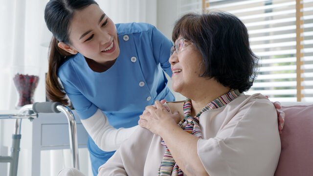 Young asian woman or nurse home care hand on senior grandmother shoulder give support empathy to elderly lady or older people in assisted living homecare mental health sick relief concept.
