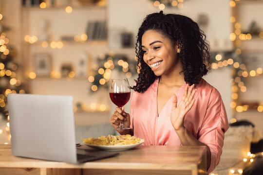 Black woman having dinner drinking wine making videocall