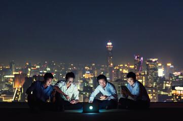 Obraz Smiling Businessmen Using Laptop While Sitting On Building Terrace At Night - fototapety do salonu