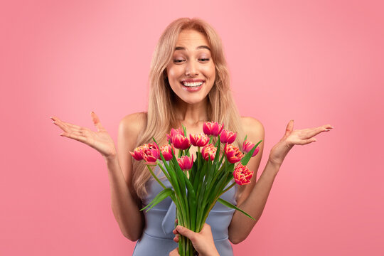 Gorgeous young lady feeling excited to receive bunch of tulips for Woman's Day on pink studio background