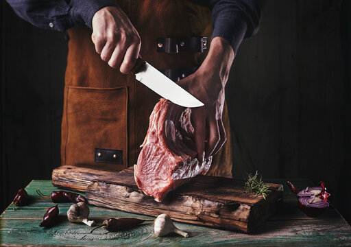 A guy in a leather apron is slicing raw meat. The butcher cuts the pork ribs. Meat with bone on a wooden cutting board..
