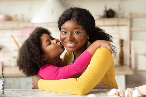 Happy Mother's Day. Little Black Girl Kissing Her Happy Mom In Kitchen