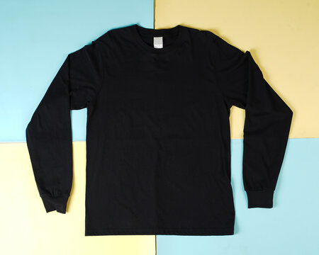 Pile of black folded clothes. Top view of folded black t-shirt isolated with colored background, copy space, flat lay. Blank t-shirt templates are commonly used for mockups and template designs.