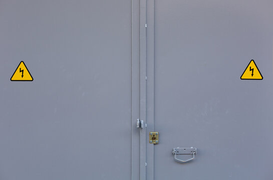 Gray iron door with yellow electricity signs.