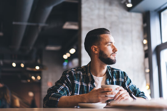 Pensive Caucasian millennial 20 years old holding tea cup in hands resting in cafeteria during free time, thoughtful male customer dressed in trendy shirt looking away during coffee time in local