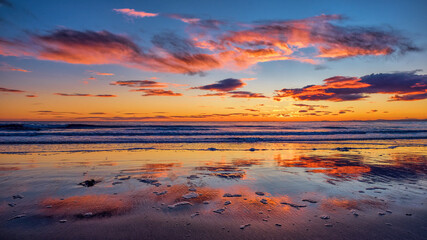 Sunrise over the North Sea off Brora beach in the Highlands with dawn colors reflected in wet sand