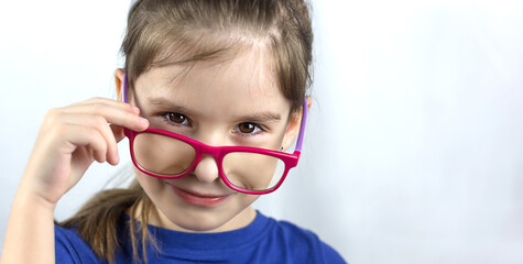 Health care, eyeball check, clear vision concept. Close up portrait of charming schoolgirl in red and purple glasses