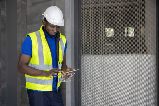 Black  Enigineer Wearing White Hard Hat Looking at His Tablet at the Construction Site