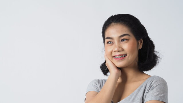 Oral Care. Dental brace teenager girl smile and looking to camera. white teeth with blue braces. Dental care. Asian woman with contact lens and orthodontic accessories. Cosmetic dentistry. white BG