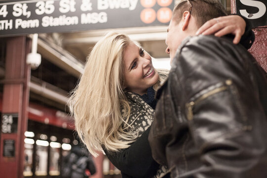 Smiling girlfriend embracing boyfriend while standing at subway station