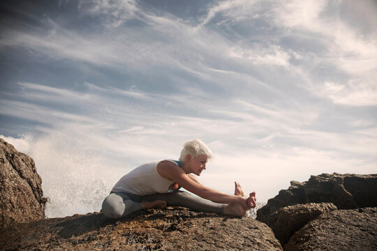Blond flexible woman practicing yoga on rock formation at beach against sky