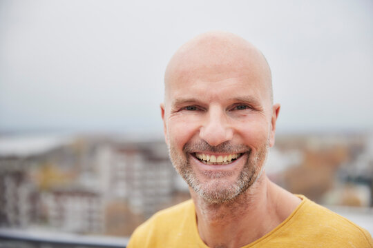 Mature man smiling while standing on rooftop