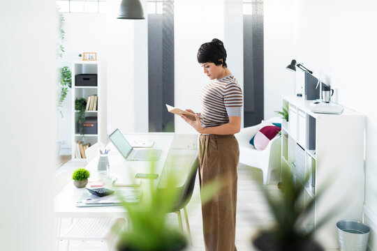 Portrait of businesswoman browsing documents in front of office table