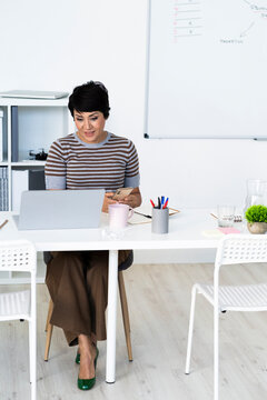Portrait of businesswoman sitting at office table with smart phone in hands