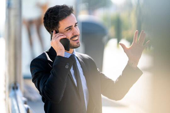 Smiling businessman gesturing while talking on mobile phone outdoors