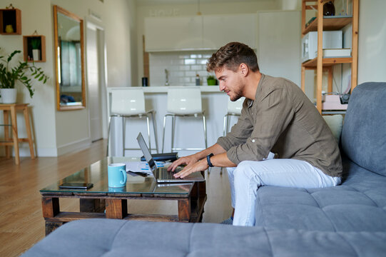 smiling male entrepreneur working at home with laptop while sitting on sofa in living