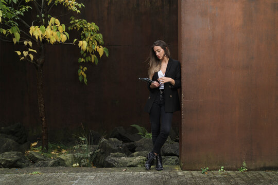 Fashionable businesswoman using digital tablet while leaning on brown wall