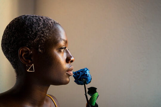 Thoughtful woman with blue rose looking away by white wall