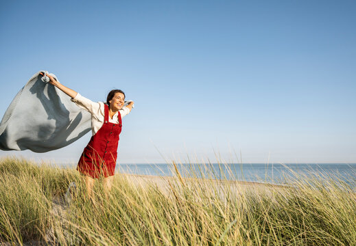 Young woman with arms outstretched holding shawl while standing at beach