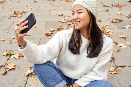 Smiling woman looking at video call on mobile phone while sitting on footpath