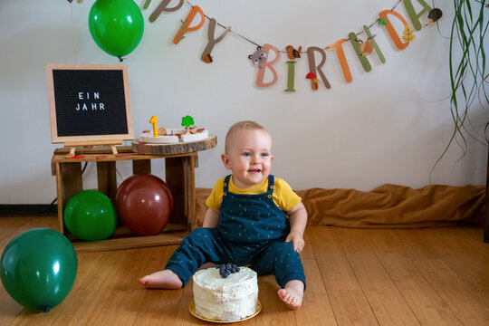 Smiling baby boy sitting with cake on floor against decoration at home