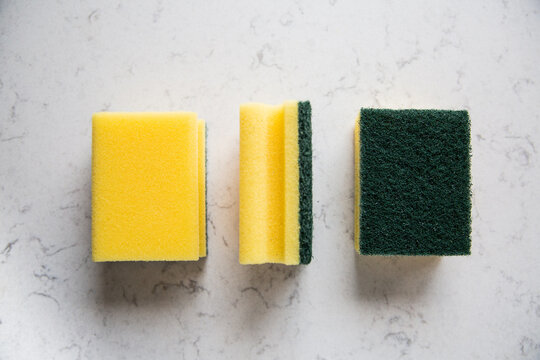 Kitchen sponges on a marble kitchen counter, top view.