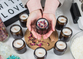 Fototapeta Hands hold a handmade ecological and vegan soy wax candles with dried flowers. Amber and opaque container. Cruelty-free vegan product. obraz