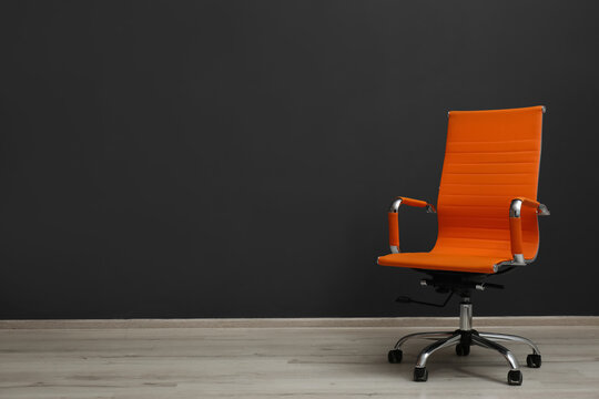 Comfortable office chair near black wall indoors. Space for text