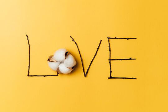 Creative flat lay of word love on yellow background with baumwolle