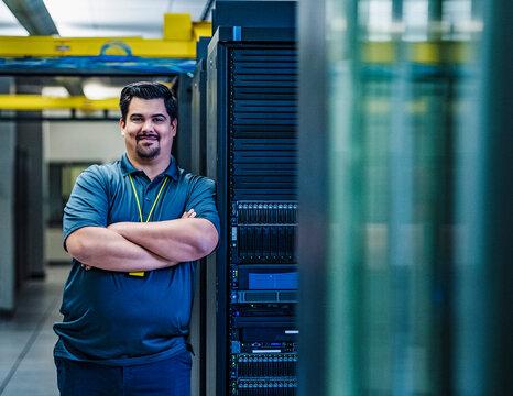 Smiling employee standing in data center