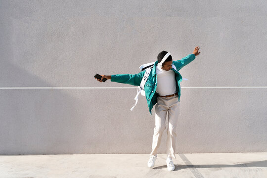 Carefree man with headphones and mobile phone dancing with arms outstretched against gray wall