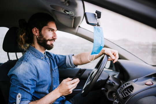 Smiling young man sitting in car while holding smart phone during COVID-19