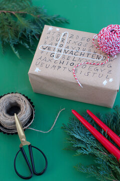 Scissors, string and word search puzzle on wrapped Christmas present