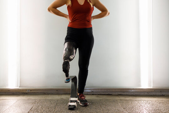 Athlete with prosthetic leg standing against wall in underpass