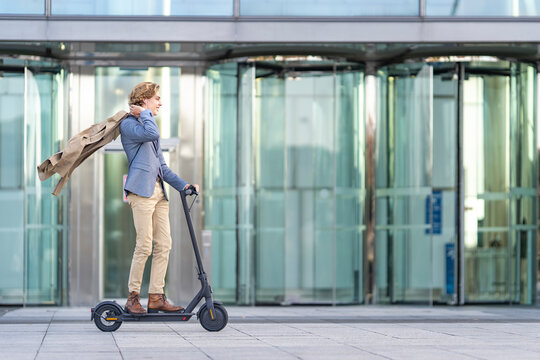 Carefree businessman riding electric push scooter on footpath