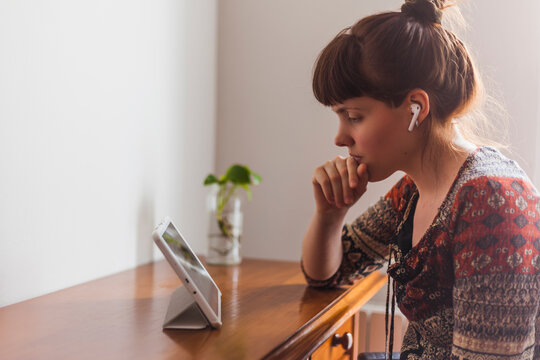 Young woman e-learning through digital tablet with wireless earphones in living room at home