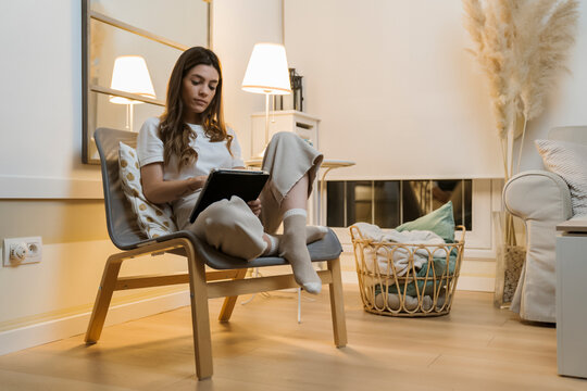 Woman using digital tablet while sitting on chair at home