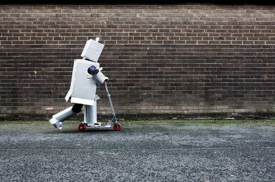 Boy dressed as robot riding scooter